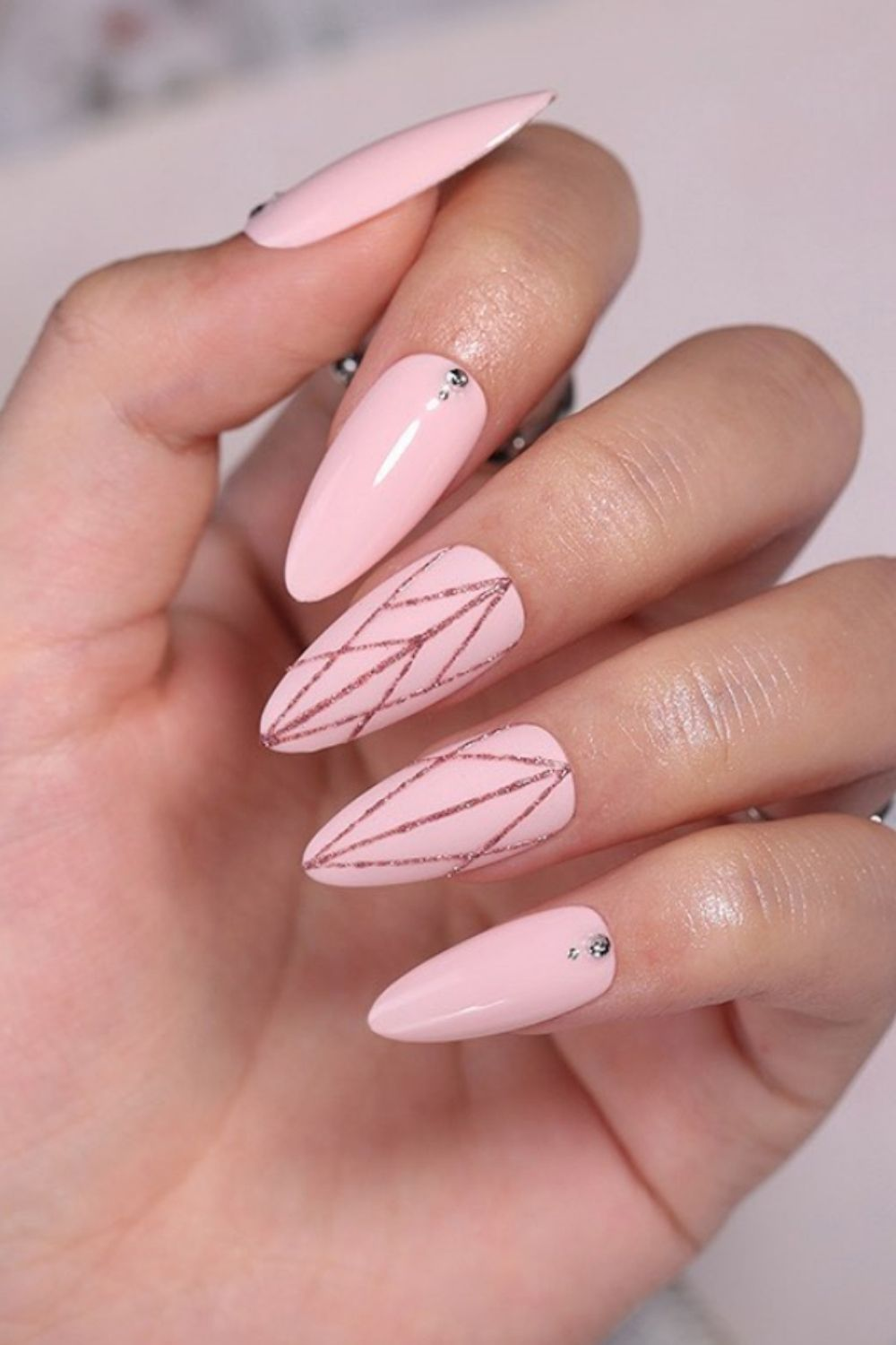 A geometric almond nail design in pink and gold